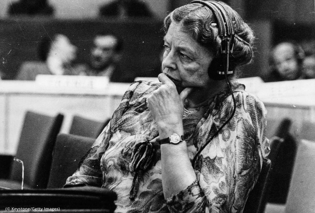 Eleanor Roosevelt memakai pelantang dan menopang wajahnya dengan tangan (© Keystone/Getty Images)