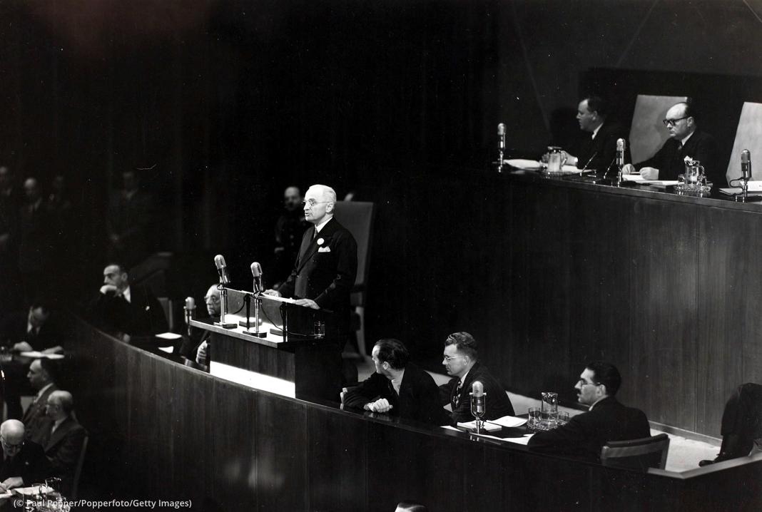 Presiden Truman berdiri dan berbicara di podium dengan sejumlah orang yang duduk di sekelilingnya mendengarkan (© Paul Popper/Popperfoto/Getty Images)