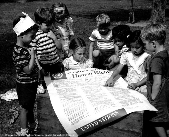 Anak-anak melihat salinan besar Pernyataan Umum tentang HAM (© Universal History Archive/Getty Images)