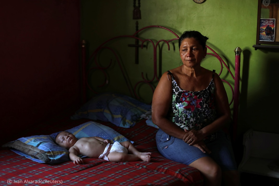 Woman sitting on bed next to baby (© Ivan Alvarado/Reuters)