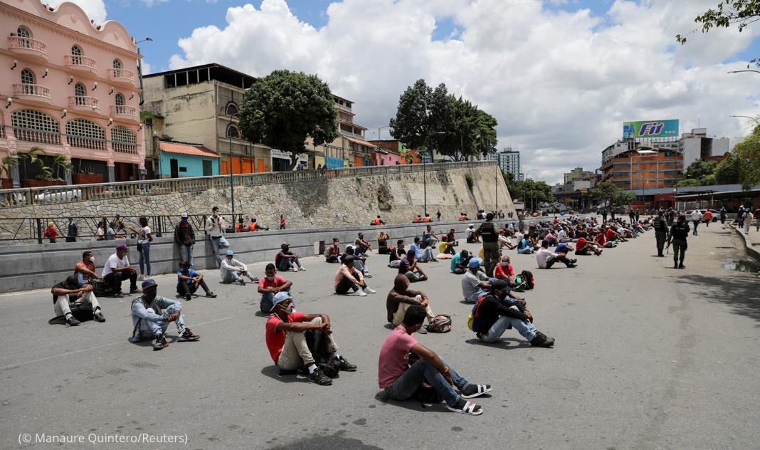 Soldados vigilando a personas sentadas en la calle (© Manaure Quintero/Reuters)