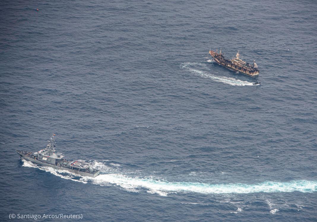 Una nave circula alrededor de un barco de pesca (© Santiago Arcos/Reuters)