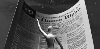 Illustration of human figure standing in front of image of Universal Declaration of Human Rights