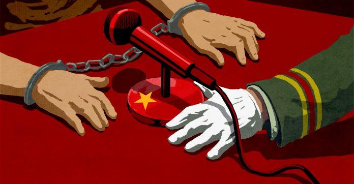 Руки в наручниках на столе возле микрофона, который держит рука в перчатке (State Dept./D. Thompson)