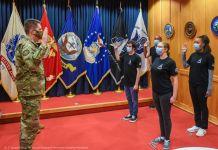 Deretan bendera di samping pria berseragam kamuflase yang berdiri menghadap empat orang yang mengangkat tangan untuk bersumpah (Angkatan Antariksa AS/Sersan Teknis Armando Schwier-Morales)