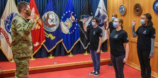 Un homme en treillis militaire face à quatre personnes, tous la main droite levée, avec une rangée de drapeaux en arrière-plan (U.S. Space Force/Technical Sergeant Armando Schwier-Morales)