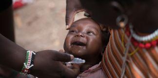 Un bebé sonríe mientras un adulto sostiene la ampolla de una vacuna oral (USAID/MCSP/Allan Gichigi)