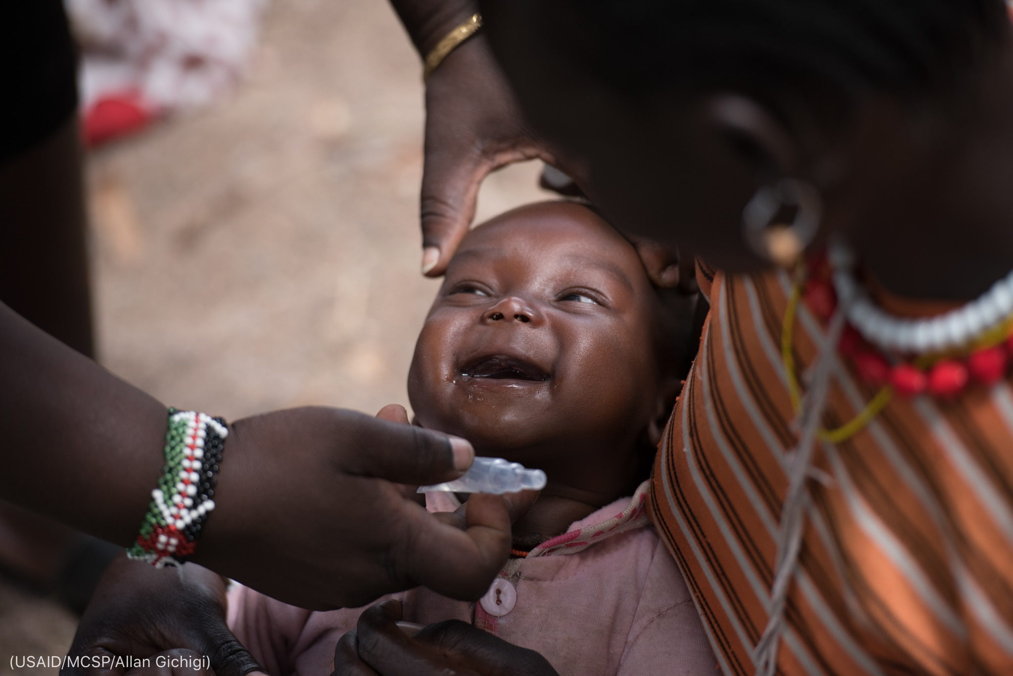 Baby smiling while adult holds plastic vial (USAID/MCSP/Allan Gichigi)