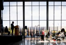 A man standing on stage at a lectern against a large bank of windows (Homeland Security Dept./Benjamin Applebaum)