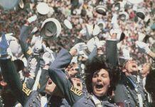 Kadet wanita melempar topi ke udara bersama banyak kadet lainnya (Atas kebaikan Sue Fulton)