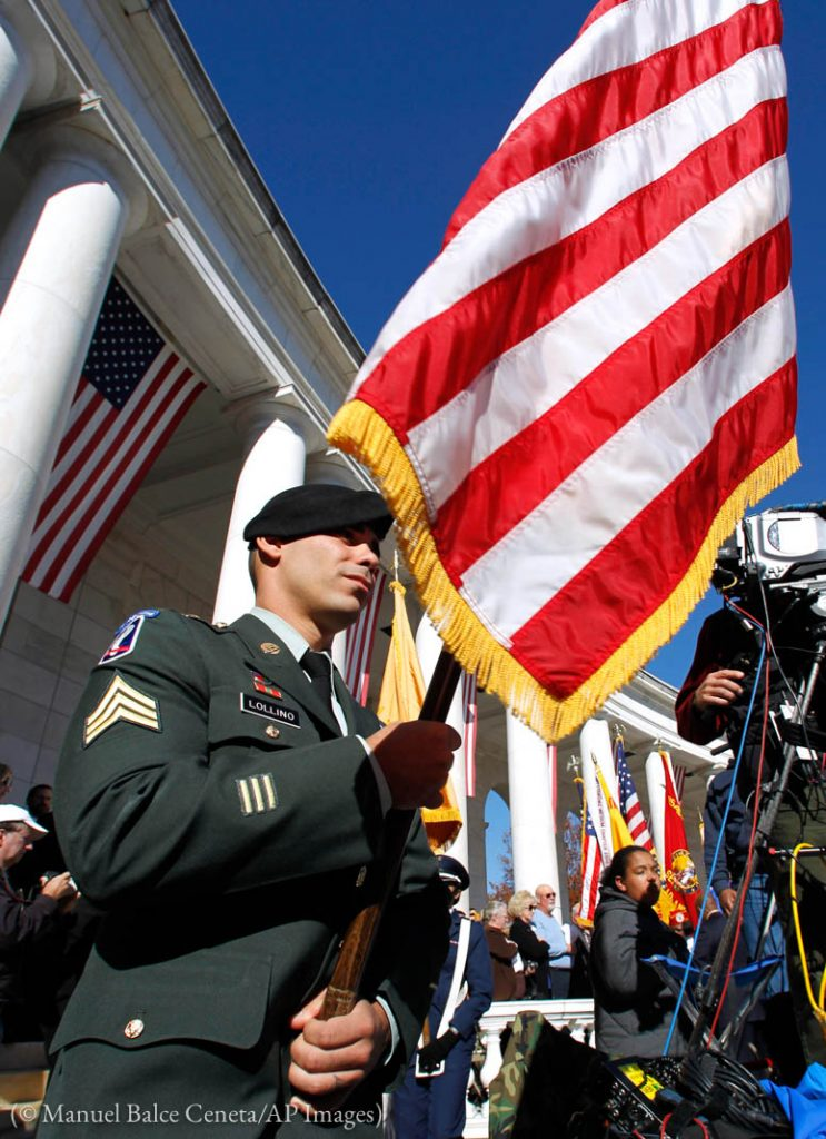 Soldier holding American flag (© Manuel Balce Ceneta/AP Images)