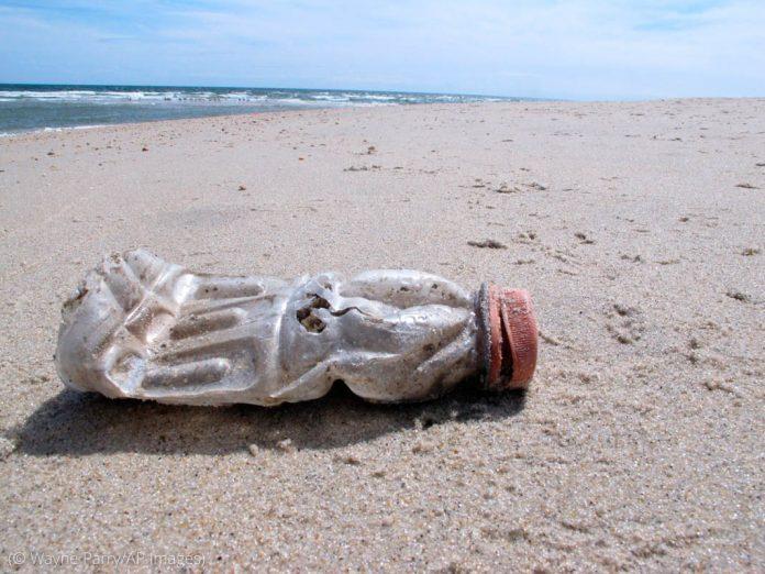ساحل پر پڑی پلاسٹک کی استعمال شدہ بوتل (© Wayne Parry/AP Images)