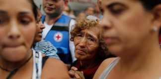 Woman looking through crowd of people (© Ariana Cubillos/AP Images)