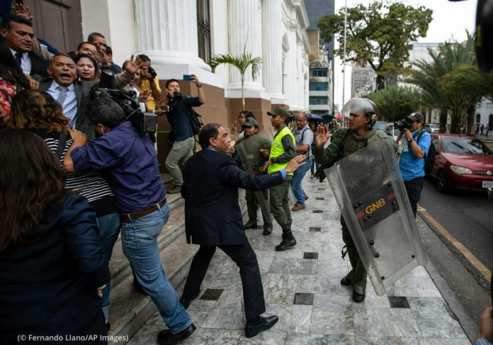 People struggling with each other outside of a building (© Fernando Llano/AP Images)