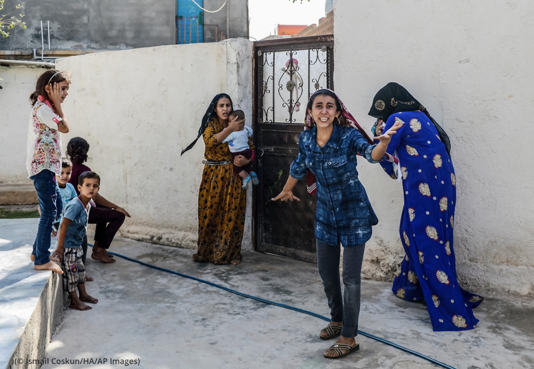 Pequeño grupo de personas de pie junto a una pared gesticulando con miedo (© Ismail Coskun/HA/AP Images)