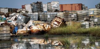 Hazardous waste containers piled up near water (© Sam Mednick/AP Images)