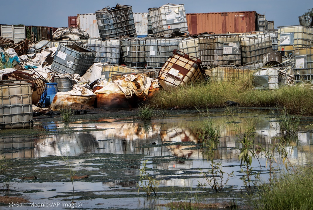 پانی کے قریب خطرناک مواد والے کنٹینروں کا لگا ہوا ڈھیر (© Sam Mednick/AP Images)