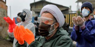 人们穿戴着防护服、面罩和手套做礼拜(© Ebrahim Noroozi/AP Images)