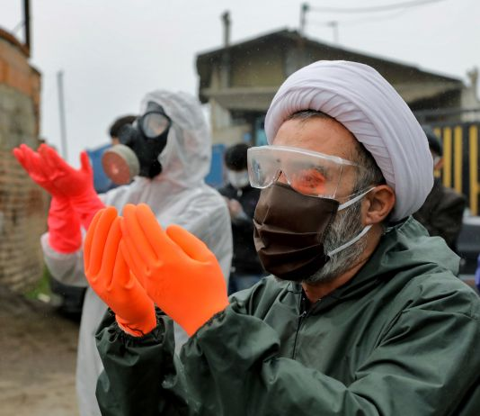 People wearing protective suits, face masks and gloves, praying (© Ebrahim Noroozi/AP Images)