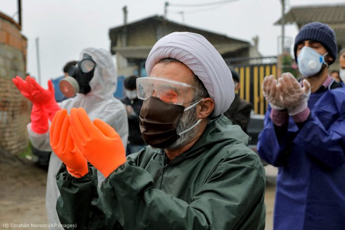 Three people wearing protective suits, face masks and gloves, praying (© Ebrahim Noroozi/AP Images)