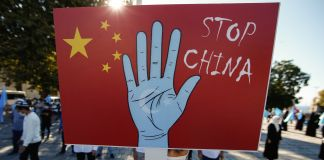 "A protester holding a sign that has a blue hand on a Chinese flag background with the words ""Stop China"" (© Emrah Gurel/AP Images)"