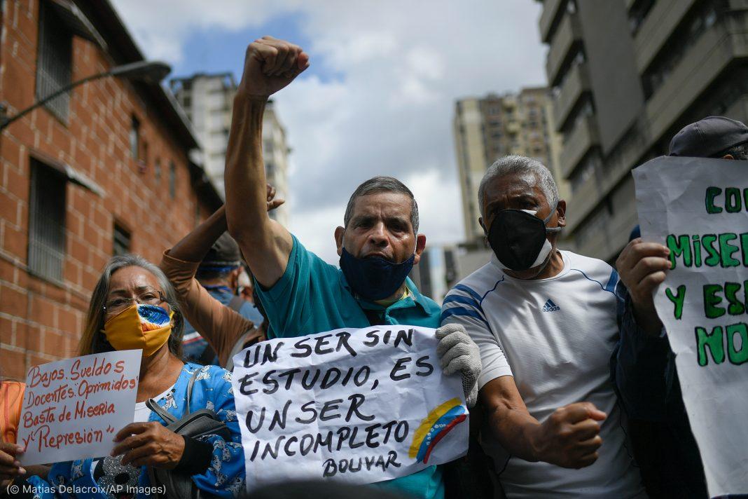 Group of protesters holding signs, raising fists, shouting slogans (© Matias Delacroix/AP Images)