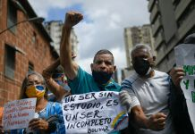 Group of protesters holding signs, making fists, shouting (© Matias Delacroix/AP Images)