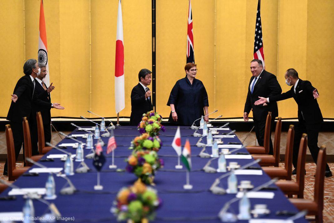 Cinco homens e uma mulher em pé ao redor de uma mesa, com bandeiras ao fundo (© Charly Triballeau/AP Images)