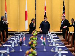Five men and a woman standing around a table, with flags in background (© Charly Triballeau/AP Images)