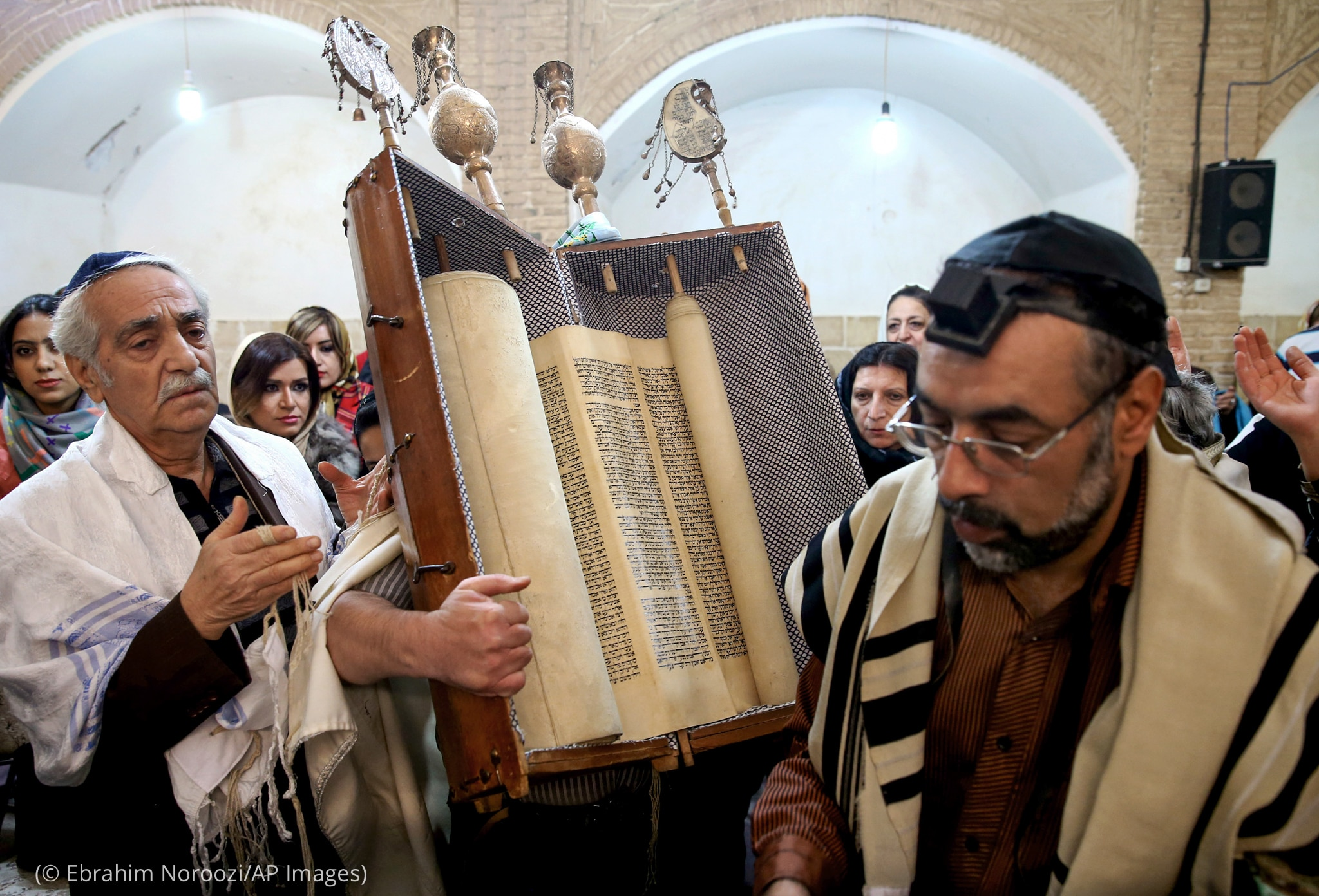 Man holding large box containing scrolls with other people around him (© Ebrahim Noroozi/AP Images)
