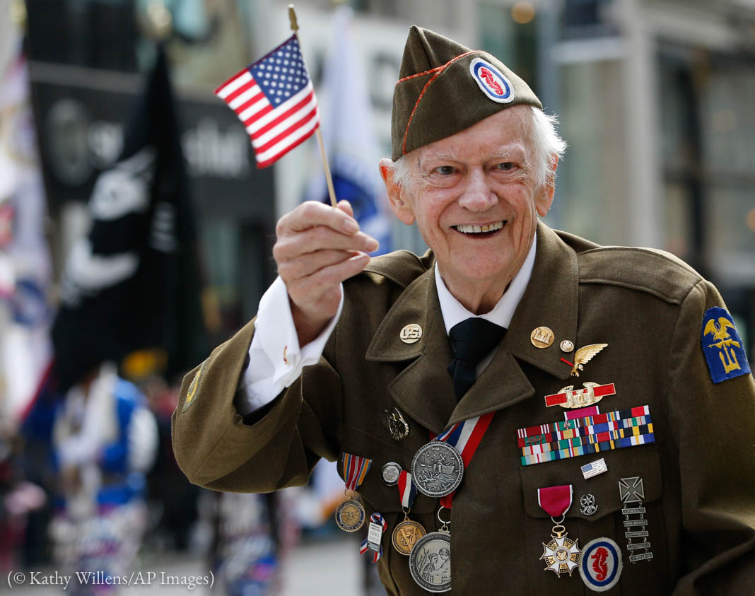 Veteran soldier waving an American flag and smiling