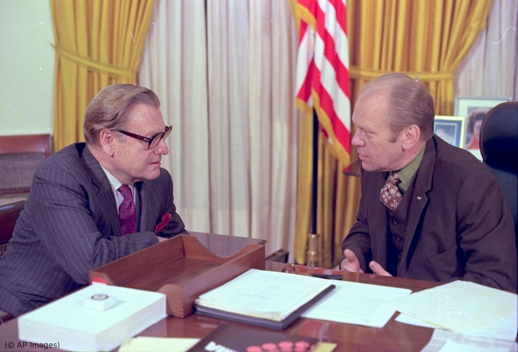 Nelson Rockefeller and Gerald Ford talking at desk (© AP Images)