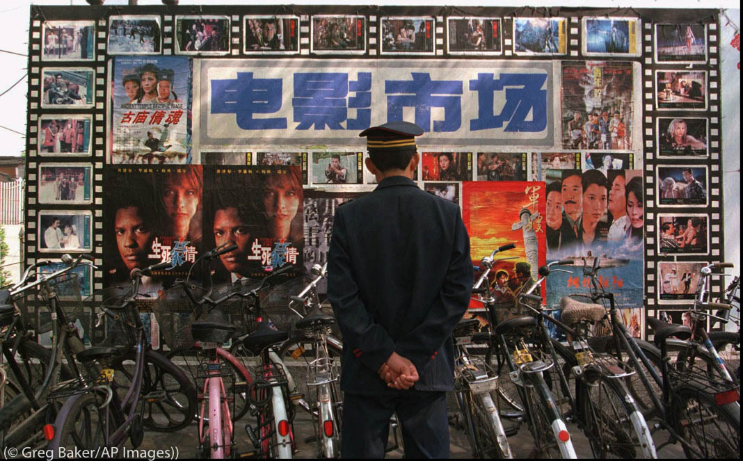 Security guard looking at movie posters behind row of bicycles (© Greg Baker/AP Images)