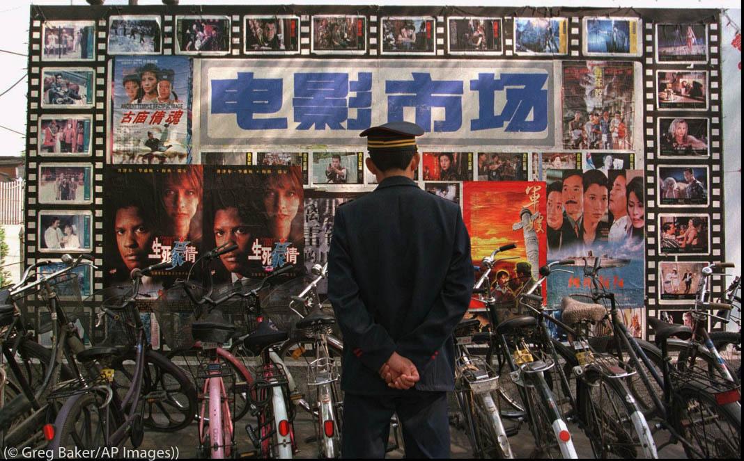 Segurança olha cartazes de filmes atrás de uma fileira de bicicletas (© Greg Baker/AP Images)