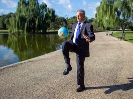 Man on wide path next to pond bouncing globe-painted soccer ball on his knee (State Dept./D.A. Peterson)