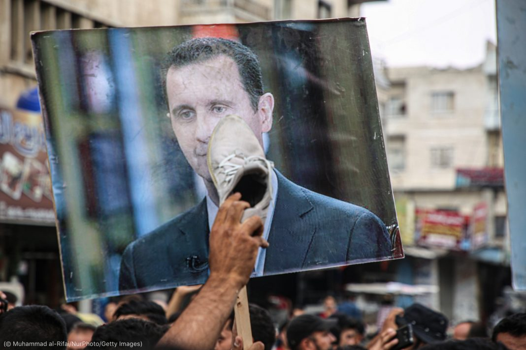 Person rubbing a shoe on a picture of Bashar al-Assad at a protest (© Muhammad al-Rifai/NurPhoto/Getty Images)