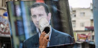 Person rubbing shoe on picture of Bashar al-Assad (© Muhammad al-Rifai/NurPhoto/Getty Images)