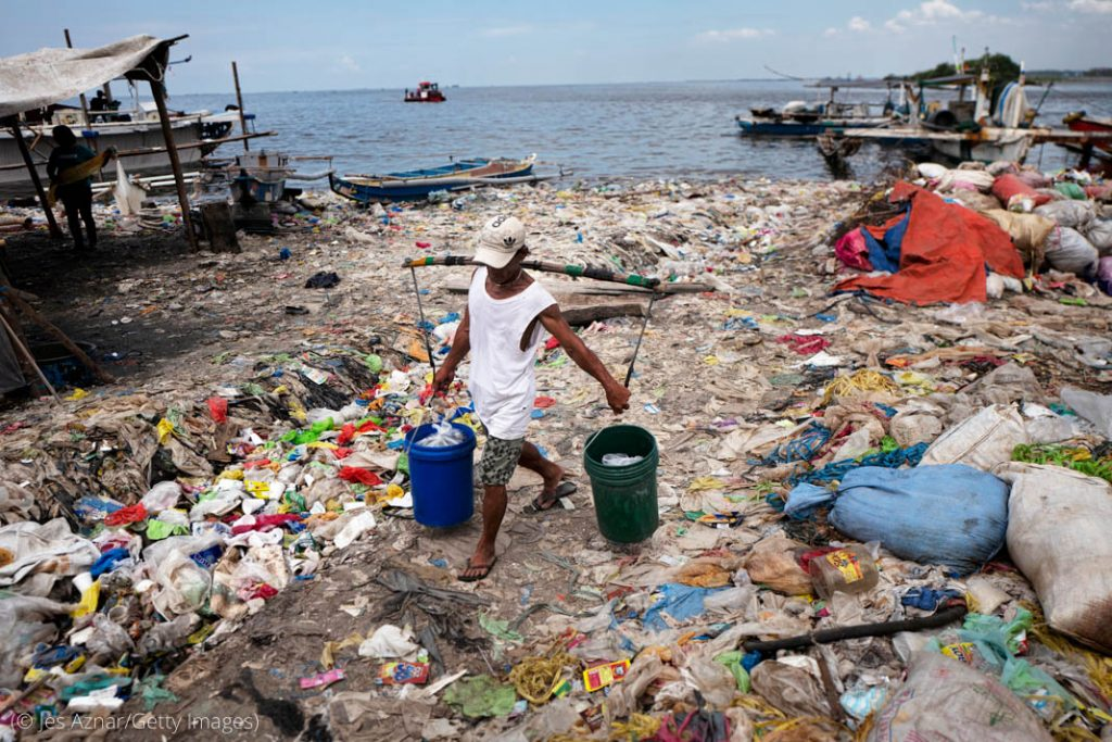 کچرے سے اٹے ساحل میں سے ایک آدمی دو بالٹیاں اٹھائے جا رہا ہے (© Jes Aznar/Getty Images)