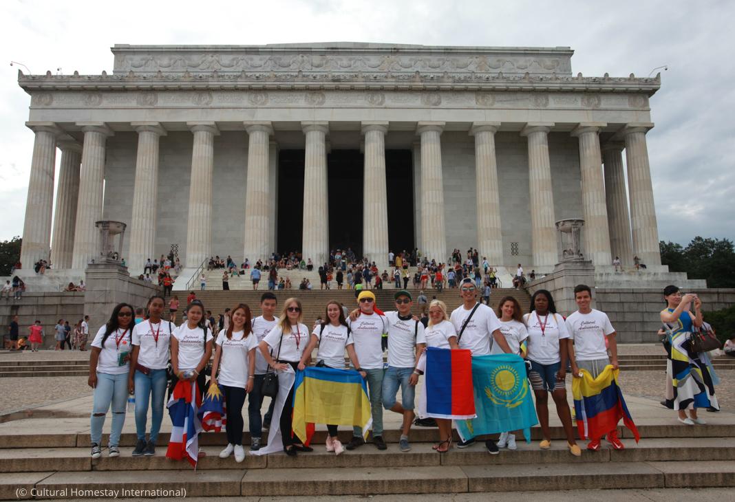 مجموعة من الأشخاص يحملون الأعلام أمام نصب لنكن التذكاري (© Cultural Homestay International)