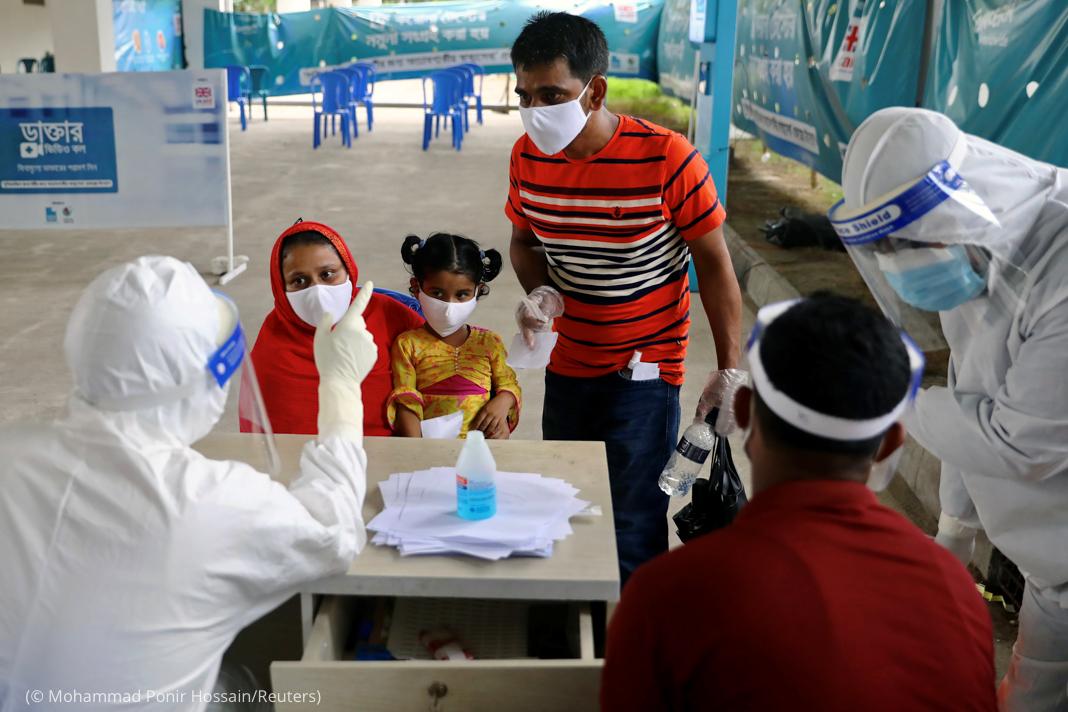 Personas con mascarillas en mesa frente a otras con equipo de protección pesado (© Mohammad Ponir Hossain/Reuters)