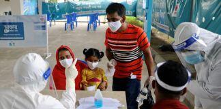 Un couple et un enfant portant tous un masque face à des personnes en équipement de protection individuelle, une table séparant les deux groupes (© Mohammad Ponir Hossain/Reuters)