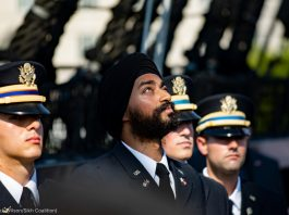Sikh soldier with religious headwear looking into the sky during ceremony with other soldiers wearing military hats (© Mark Wilson/Sikh Coalition)