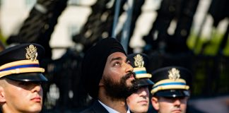 Bearded soldier wearing turban looking into sky standing with cleanshaven soldiers wearing military hats (© Mark Wilson/Sikh Coalition)