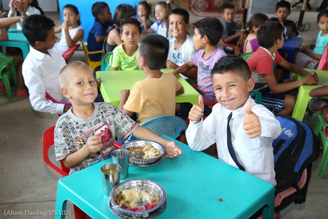 Deux petits garçons souriants assis à une table basse sur laquelle sont posées deux assiettes pleines et deux gobelets, dans une pièce remplie d'autres enfants assis à des tables basses (Alison Harding/USAID)
