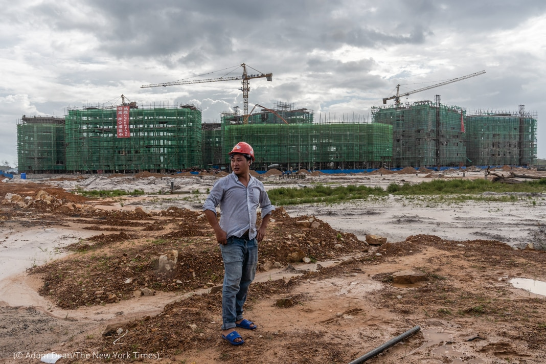 Man wearing hard hat standing in dirt in front of building under construction (© Adam Dean/The New York Times)