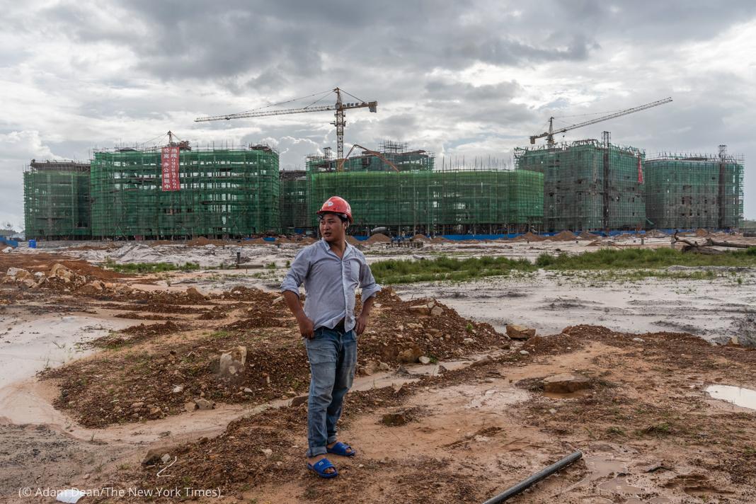 Hombre con casco de obra de pie en la tierra frente a un edificio en construcción (© Adam Dean/The New York Times)