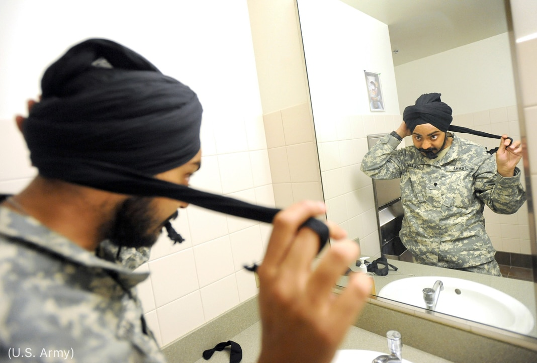 Hombre barbudo con uniforme del ejército mirándose en el espejo mientras se envuelve un turbante en un baño (Ejército de EE. UU.)