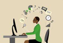 کاروباری علامات سے گھِری اور میز پر رکھے کمپیوٹر اور مانیٹر کے سامنے بیٹھی کام کرتی عورت کا تصویری خاکہ (© Naum/Shutterstock)