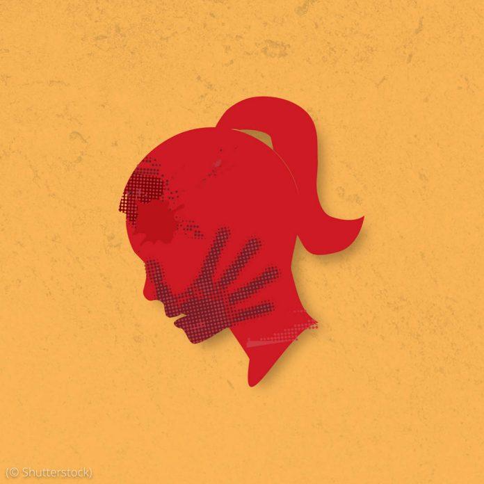 Ilustração contendo a silhueta da cabeça de uma mulher em vermelho e a impressão da palma de uma mão sobre a boca dessa mulher (© Shutterstock)