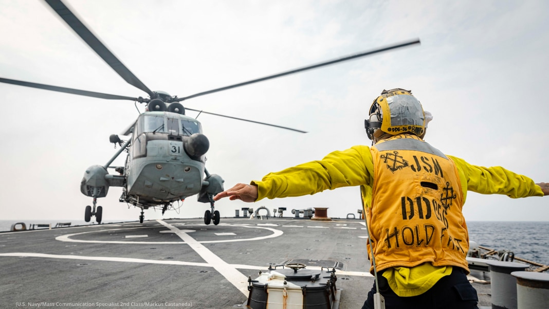 Person in safety gear signaling to helicopter landing on deck (U.S. Navy/Mass Communication Specialist 2nd Class/Markus Castaneda)